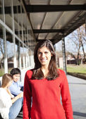 Woman Smiling With Students In Background On Campus — Stock Photo