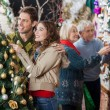 Couple Looking At Christmas Tree While Parents Shopping In Store — Stock Photo