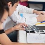 skolpojke med kalkylatorn på skrivbord — Stockfoto
