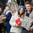 Stock Photo: Happy Couple Holding Christmas Presents With Parents In Backgrou