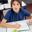 Shocked Schoolboy With Cheat Sheet Sitting At Desk — Stock Photo