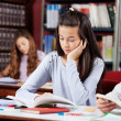 Girl Reading Book At Desk With Friends — Foto de Stock