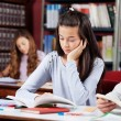 Girl Reading Book At Desk With Friends — Stock Photo
