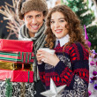 Young Couple With Disposable Cups And Christmas Presents — Stock Photo