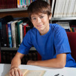 Teenage Schoolboy Smiling While Sitting In Library — Stock Photo