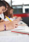 Studenti del liceo scrivendo alla scrivania — Foto Stock