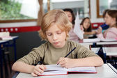 Schoolboy Writing In Book At Desk — Stockfoto