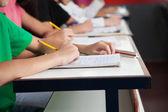Middelbare schoolstudenten schrijven op papier op Bureau — Stockfoto