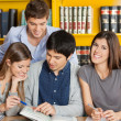 Stock Photo: Female Student With Friends Reading Book In Library