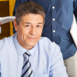 Stock Photo: Confident Teacher Smiling With Student Standing In Background At