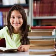 Schoolgirl Smiling While Sitting With Stack Of Books In Library — Stock Photo #33021839
