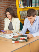 Female Student Using Mobilephone While Friend Studying In Librar — Stock Photo