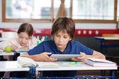 Schoolboy Using Digital Tablet At Desk — Stock Photo