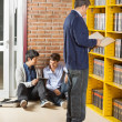 Librarian Reading Book While Students Using Digital Tablet In Li — ストック写真