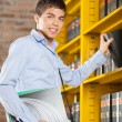 Male Student Selecting Book From Shelf In Library — Stock Photo #33057905
