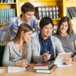 Students With Digital Tablet Discussing In College Library — Stock Photo