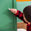 Boy Writing On Green Chalkboard In Preschool — Stock Photo