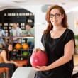 Happy Young Woman Holding Bowling Ball in Club — Stock Photo