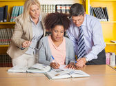 Student Writing In Book While Teachers Assisting Her At Library — Stock Photo