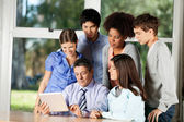Teacher Using Digital Tablet While Students Standing Around Him — Stock Photo