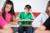 Teenage étudiants mâles se penchant sur le bureau à la salle de classe — Photo