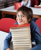 Schoolboy Resting Chin On Stacked Books At Table — Stock Photo