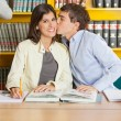 Woman Smiling While Man Kissing In Library — Stock Photo