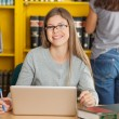 Female Student With Laptop Sitting At Table In Library — Stock Photo