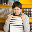 Confident Man With Stacked Books Sitting In University Library — Foto Stock