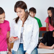 Stock Photo: Schoolgirl Listening Music While Showing Mobilephone To Classmat