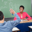 Schoolboy Raising Hand While Teacher Looking At Him — Stock Photo #33076163