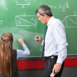 Girl Drawing Geometric Shapes On Board With Teacher Assisting He — Foto de Stock
