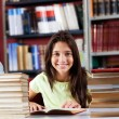 Happy Schoolgirl Sitting With Stack Of Books In Library — Stock Photo #33076643