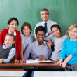 Stock Photo: Confident Teachers With Schoolchildren Together At Desk