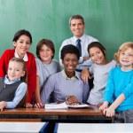 Confident Teachers With Schoolchildren Together At Desk — Stock Photo