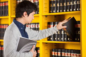 Male Student Selecting Book In Library — Stock Photo