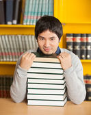 Confident Man With Stacked Books Sitting In University Library — Stock Photo