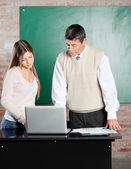 Enseignant et étudiant à l'aide d'ordinateur portable au bureau en salle de classe — Photo