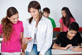 Schoolgirl Listening Music While Showing Mobilephone To Classmat — Stock Photo