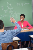 Schoolboy Raising Hand While Teacher Looking At Him — Stock Photo