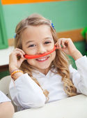 Girl Holding Mustache Made Of Clay In Preschool — Stockfoto
