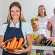 Saleswoman Holding Carrot Basket At Supermarket — Stockfoto