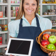 Stock Photo: SaleswomHolding Digital Tablet And Fruits Basket