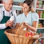 Salesman Assisting Customer Buying Groceries — Stock Photo #33099125