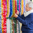 Stock Photo: Man Choosing Tinsels In Christmas Store