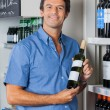 Man Displaying Wine Bottle In Supermarket — Stock Photo
