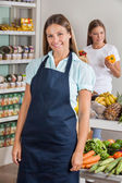 Saleswoman With Female Customer Shopping In Background — Stock Photo