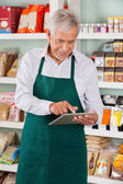 Male Owner Using Tablet In Supermarket — Stock Photo