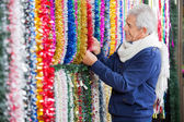 Man Choosing Tinsels In Christmas Store — Stock Photo