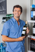 Man Displaying Wine Bottle In Supermarket — Stock Photo